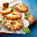 Grilled fruit pineapple slices with addition of honey on a blue wooden table